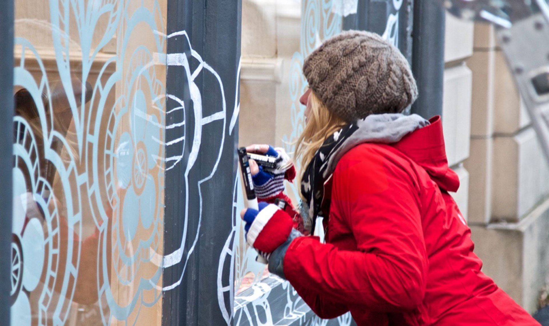 Kate George painting Bindi artwork on window