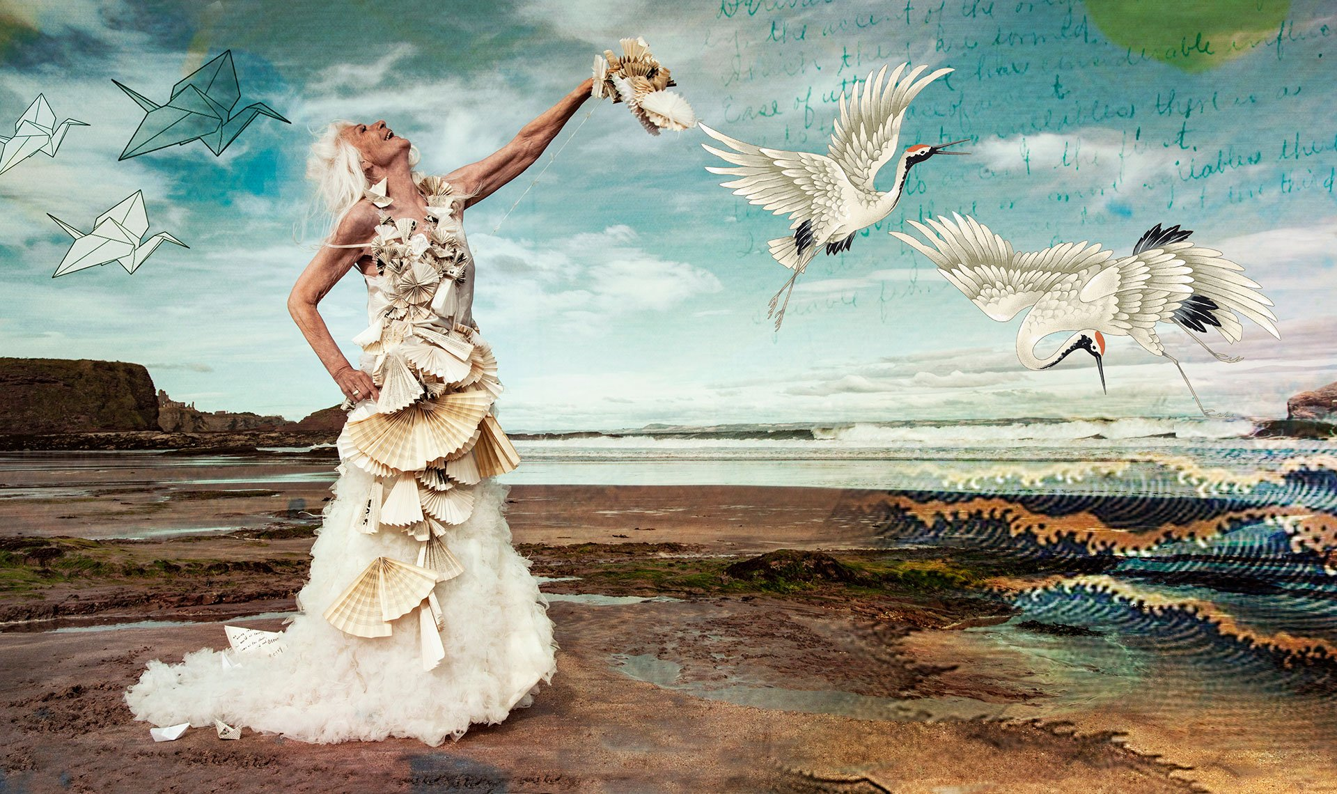 Beautiful older woman with white hair stands on beach wearing a dress made from paper fans surrounded by flying cranes image is inspired from Japanese traditional artworks